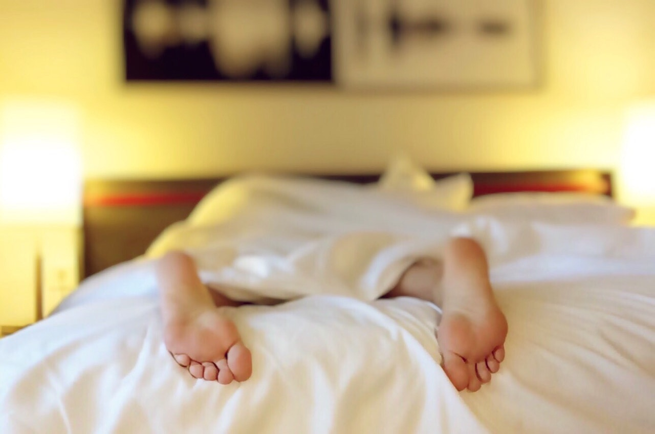 Feet of a woman laying in bed, covered with white sheet