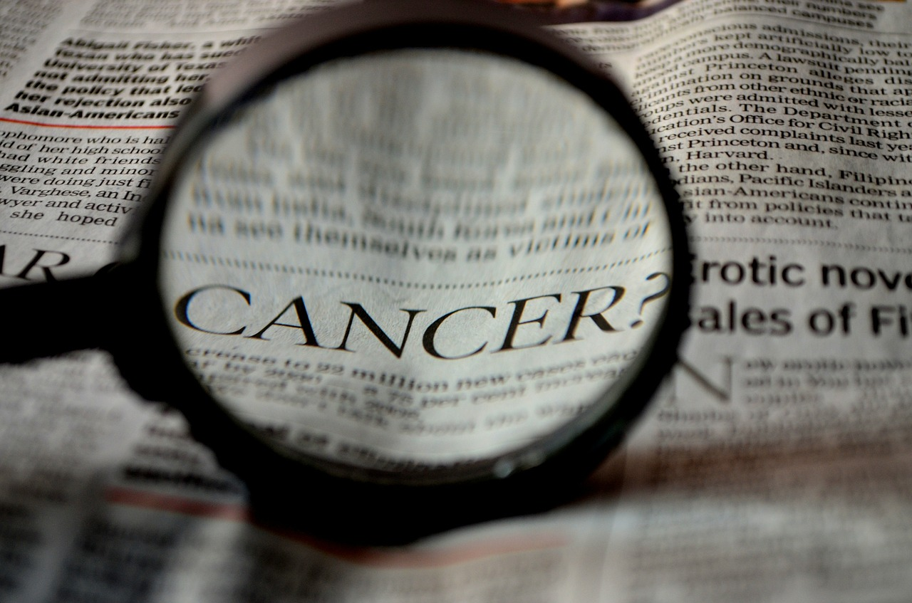 The word 'cancer' on the newspaper under the magnifying glass