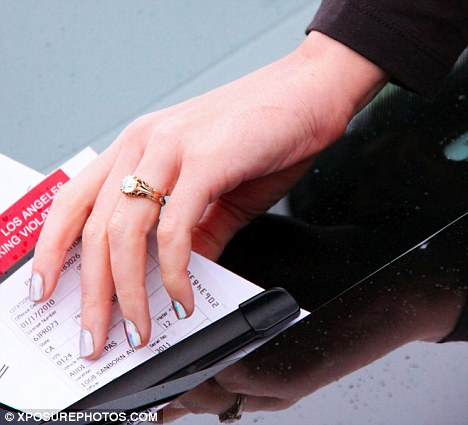 Katy Perry flashes her engagement ring as she and fiance Russell Brand are slapped with a ...