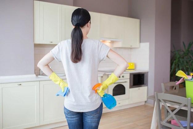 Beschäftigte frau steht in der küche und betrachtet möbel ...