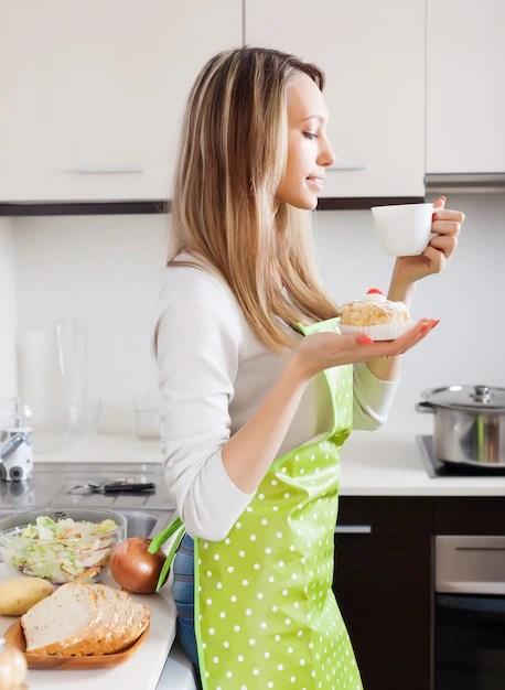 Frau mit kuchen und tee in der küche   Kostenlose Foto