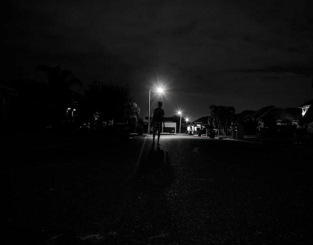 Boy walking alone at night under the street lights Photo ...