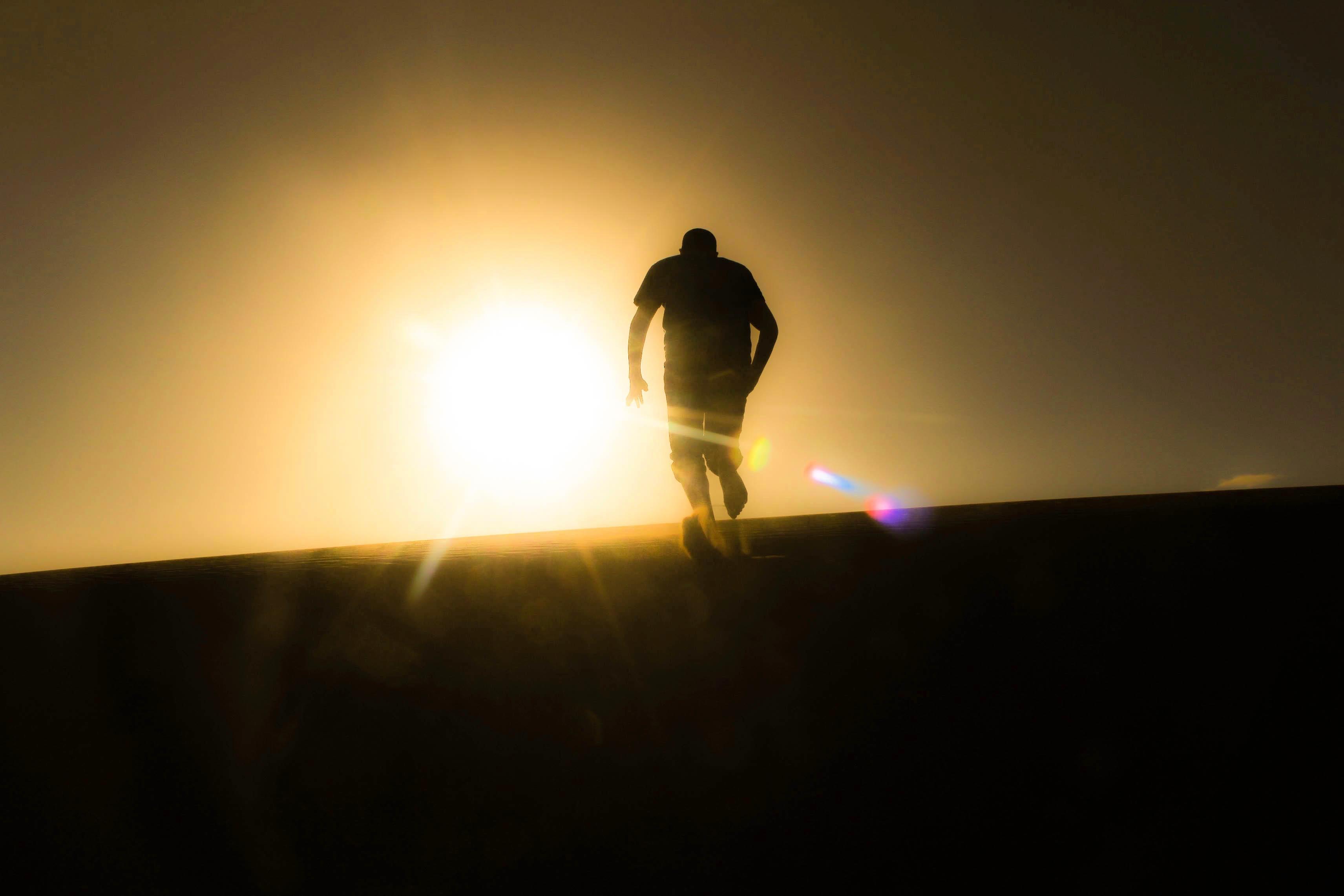 Silhouette Of Man Standing Beside Ocean During Sunset