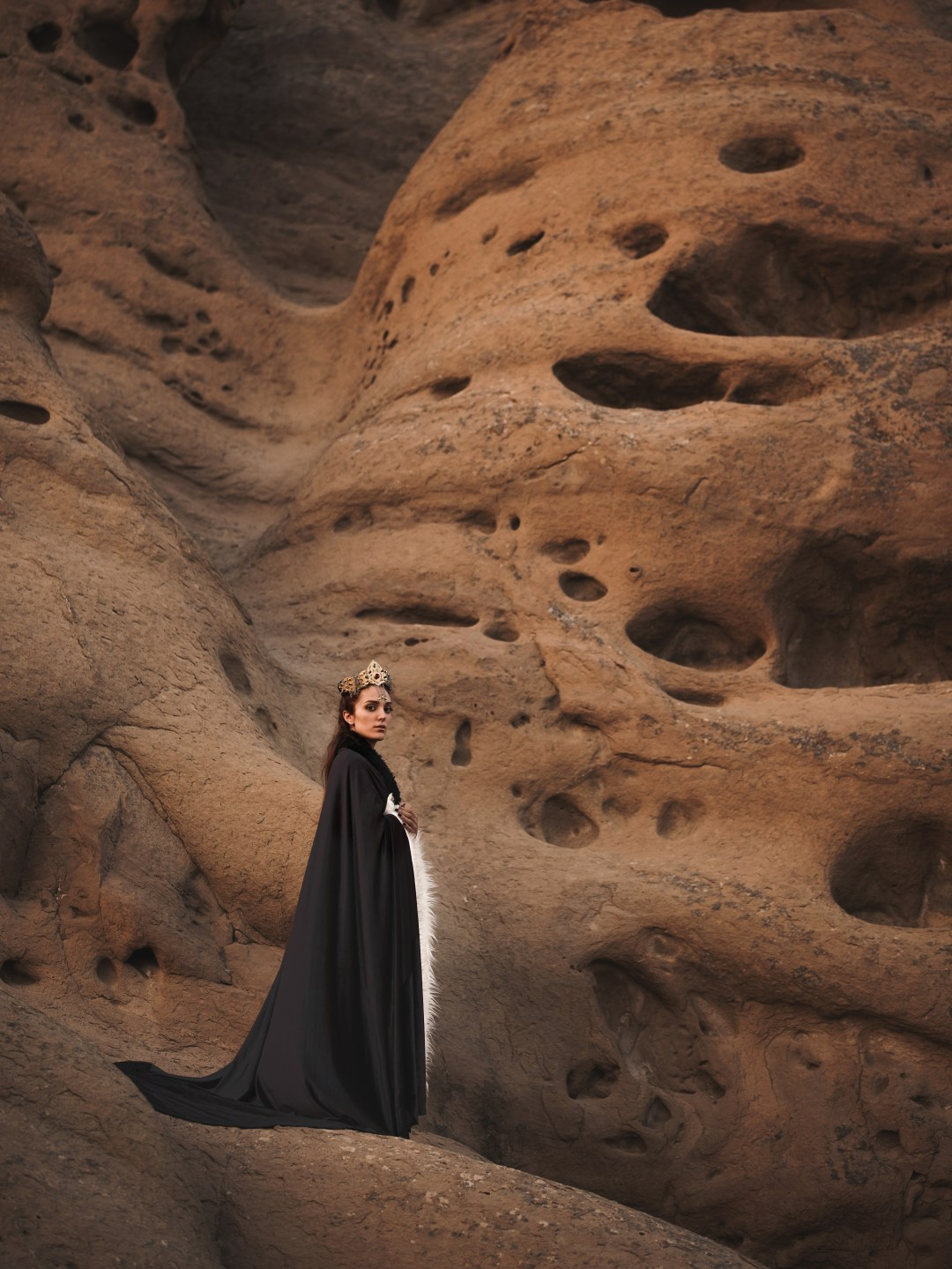 Woman In Black Cape Standing On Brown Mountain Photo