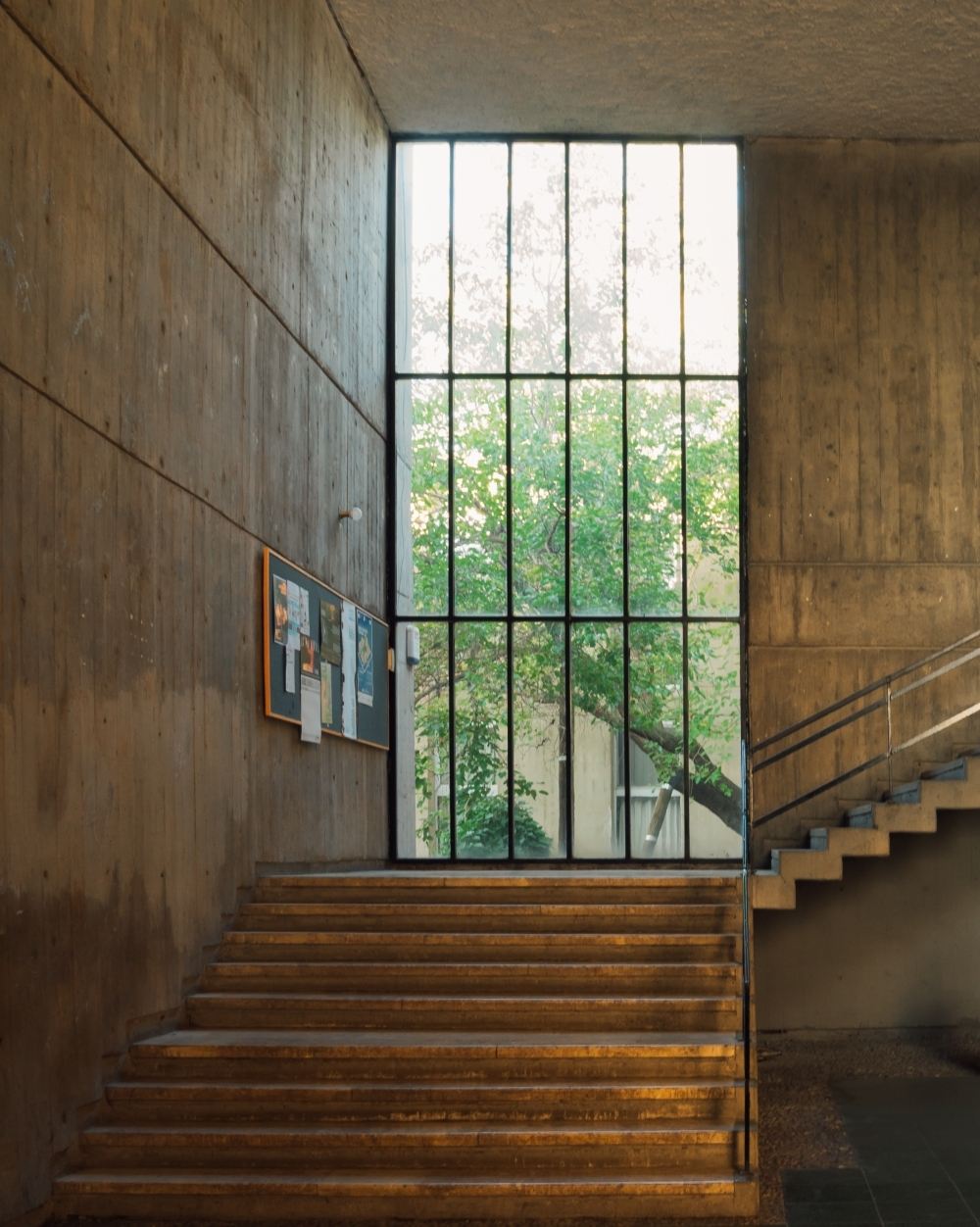 Brown Concrete Staircase Near Green Metal Window Grill Photo | Window Design For Stairs | Exterior | Kitchen Color Combination | Home Wooden Staircase | Residential | Two Story Staircase