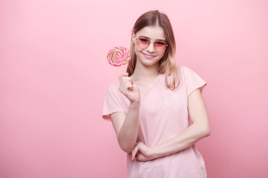 Girl with a lollipop on a pink background