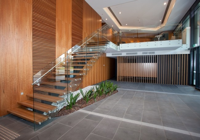 Things To Keep In Mind For Construction Of Commercial Staircases | Staircase Design For Commercial Buildings | Cylindrical Glass | Enclosed | Beautiful | Central Staircase | Sleek