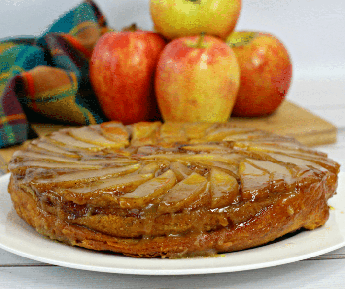 Up close picture of an apple upside down cake on a white plate