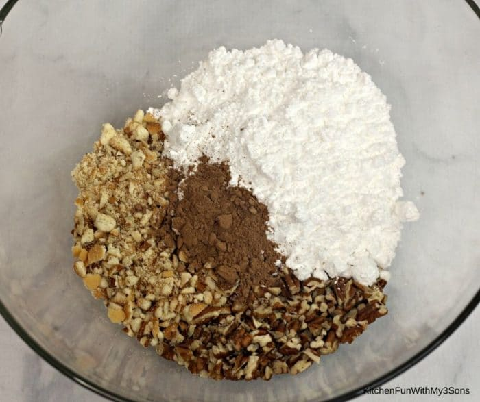 Dry ingredients for whiskey Holiday Cookie balls in a large glass bowl