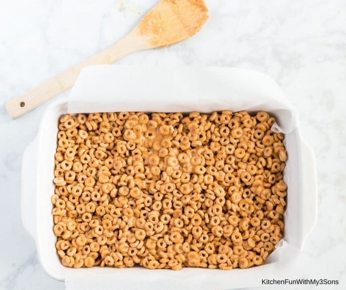 Pressing the cereal mixture down into a baking pan