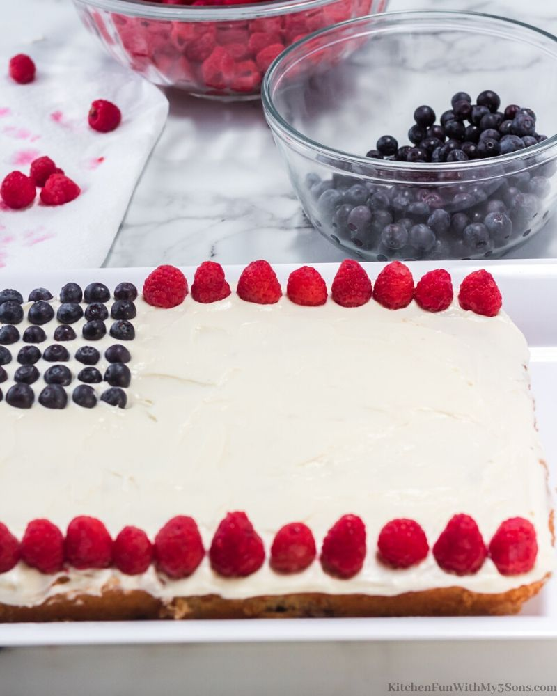 white cake with white frosting with blueberries and raspberries