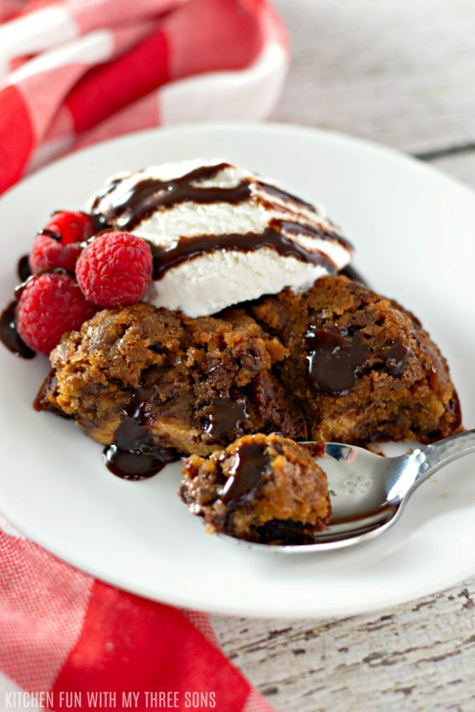 Easy Reese's Stuffed Brookie Cups on a plate with ice cream, fresh raspberries, and chocolate sauce