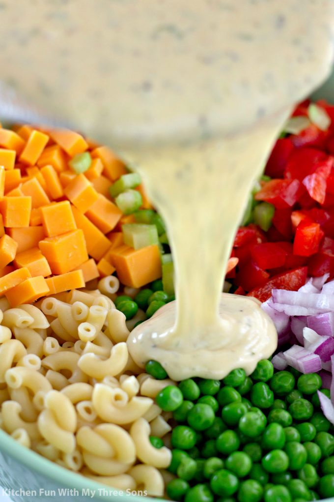 pouring dressing over macaroni salad
