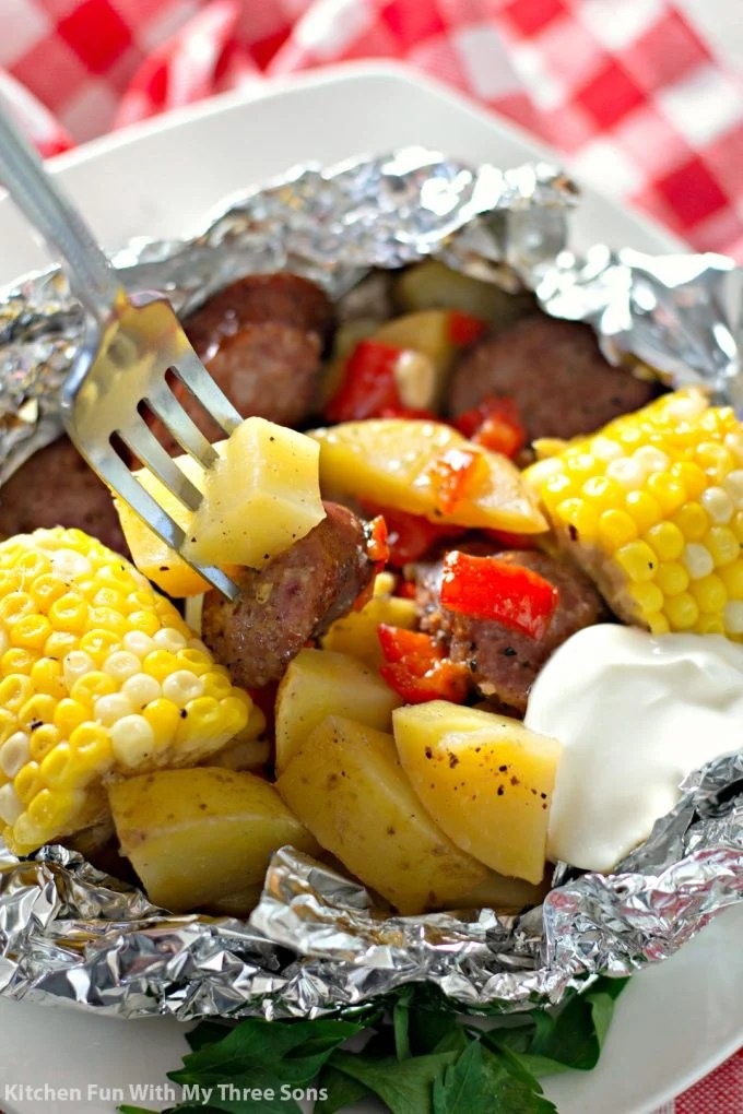 eating Garlic Kielbasa Grilled Foil Packets with a fork