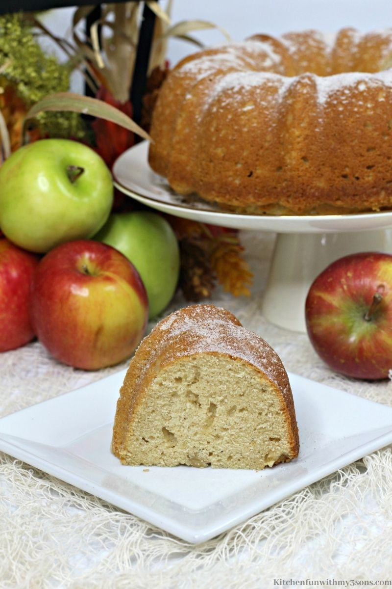 Apple Cider Doughnut Cake with apples in the background.