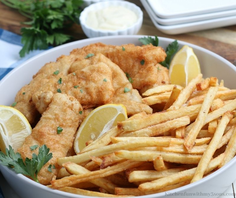 The Classic Fish and Chips Recipe garnished with cilantro and lemon.