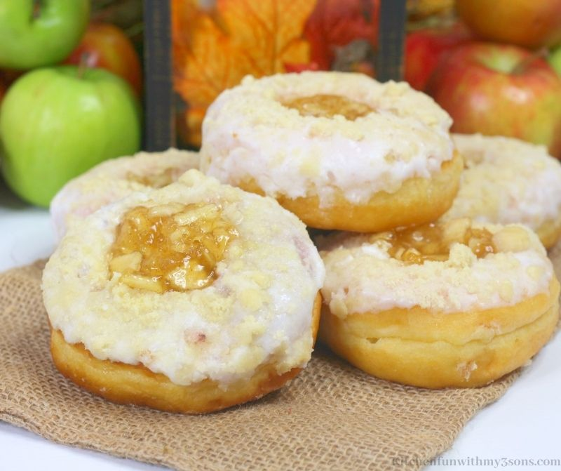 Easy Apple Donuts Recipe with framed leaves and apples behind it.