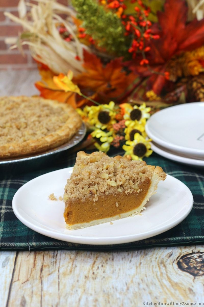 Delicious Pumpkin Streusel Pie on a plate on a patterned cloth.