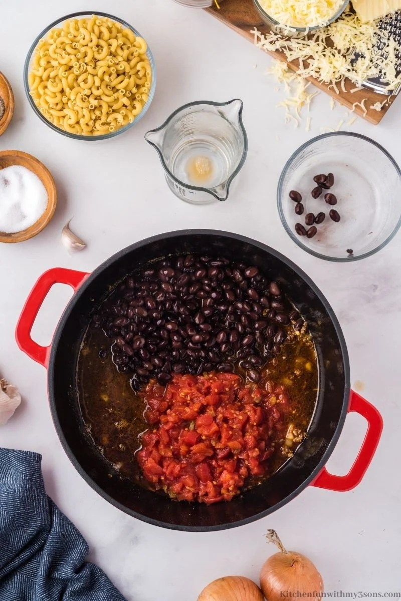 Adding the broth, beans, and tomatoes into the pot.
