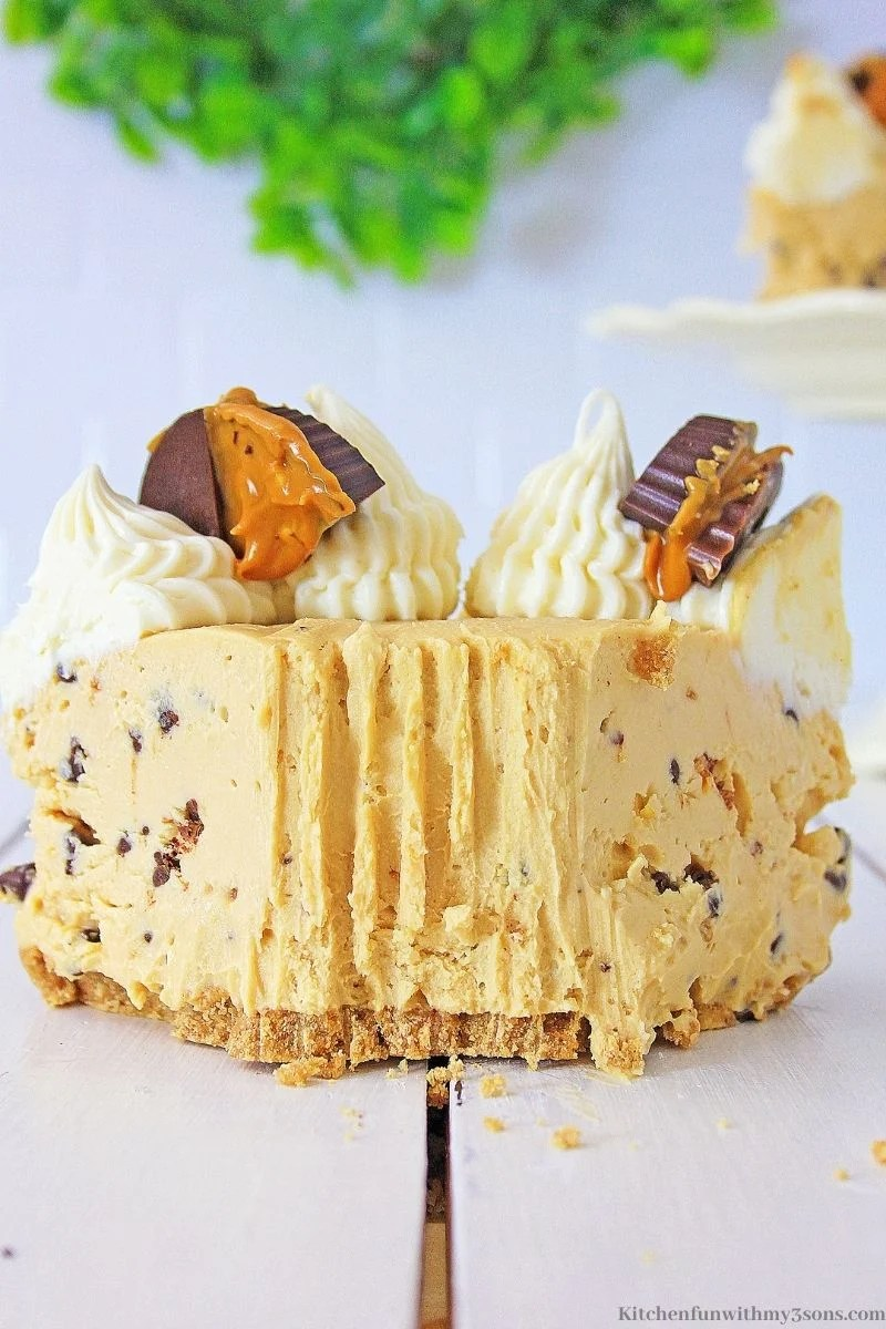 Peanut Butter Chocolate Chip Cheesecake with a bite taken out on a white wooden table.