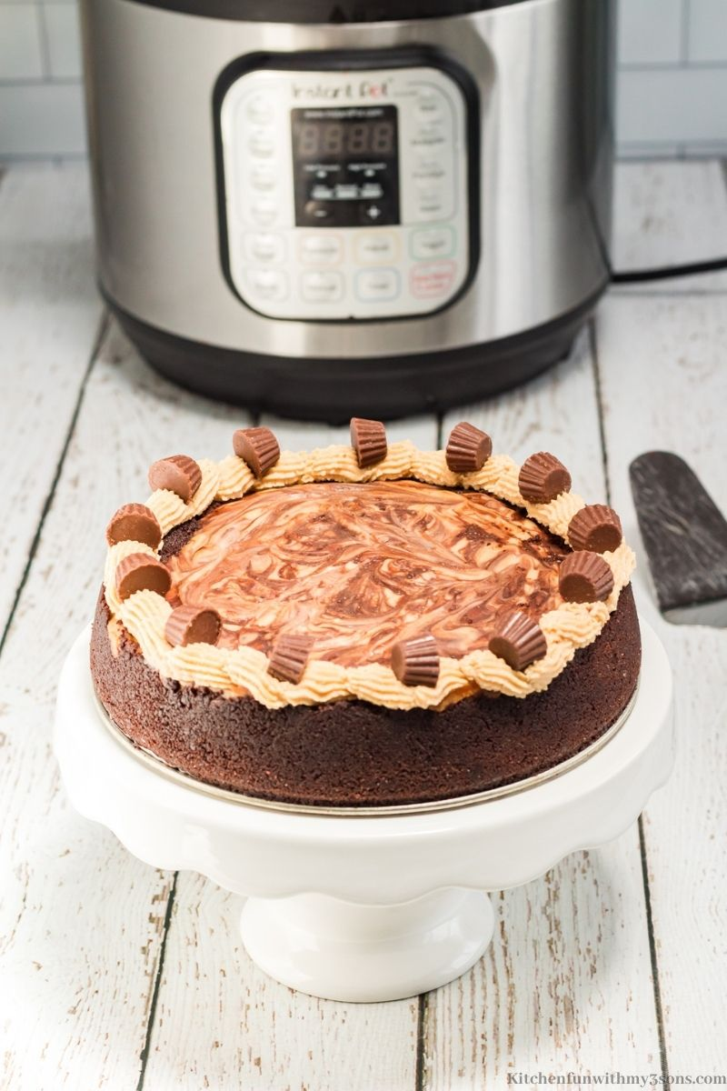 The whole Instant Pot Chocolate Peanut Butter Cheesecake on a serving stand.