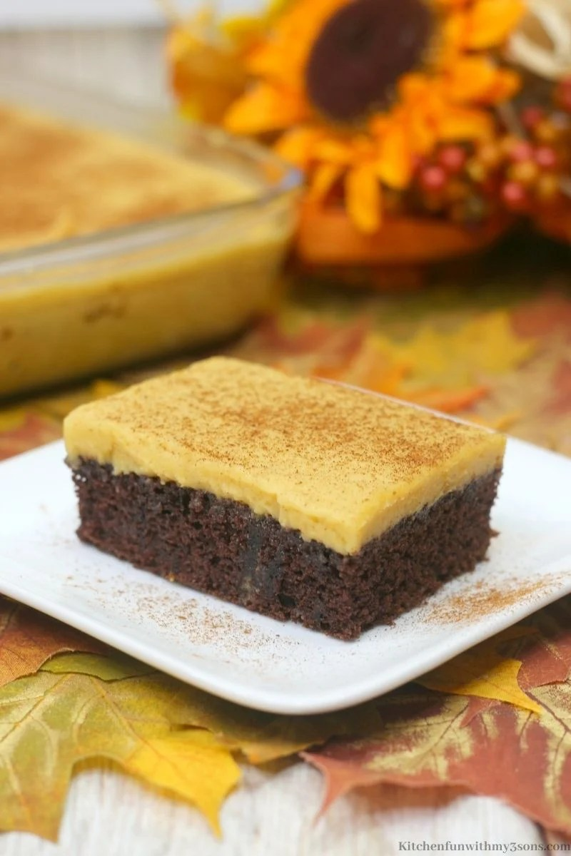 Pumpkin Chocolate Texas Sheet Cake Recipe with Fall decorations behind it.