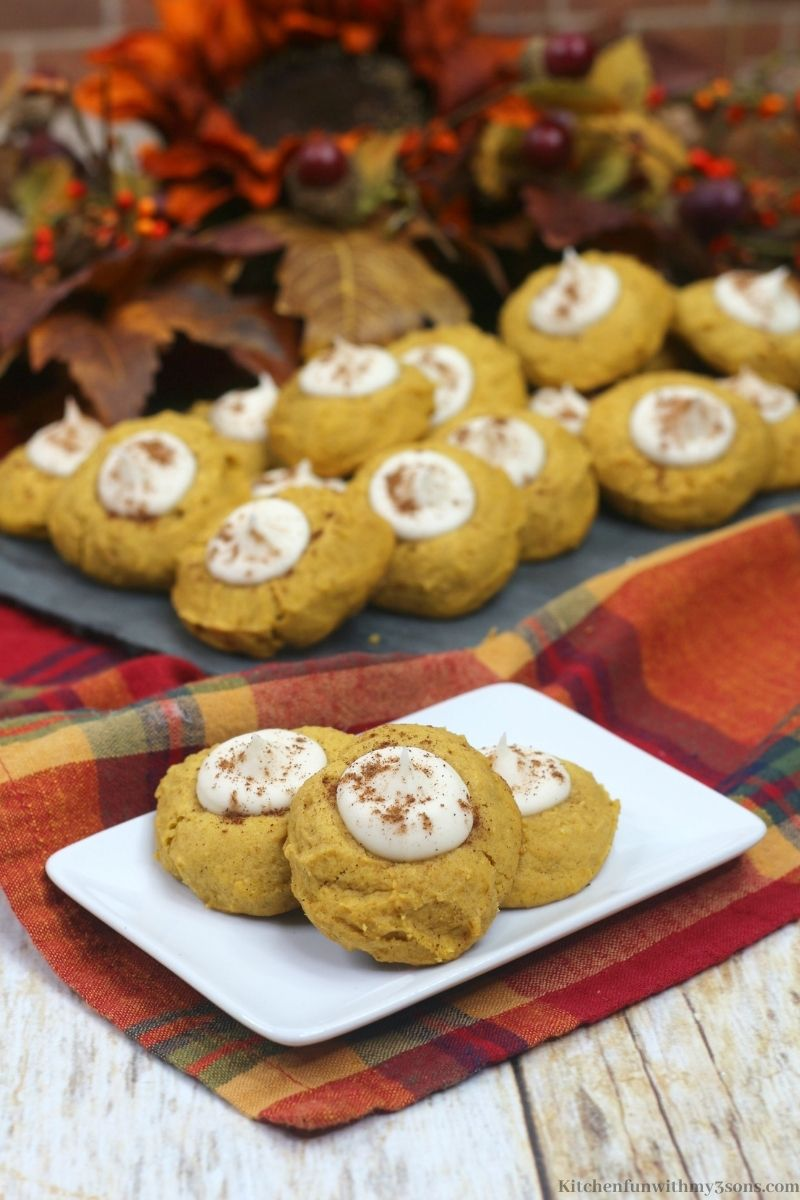 Pumpkin Thumbprint Cookies on a plate with more cookies behind it.