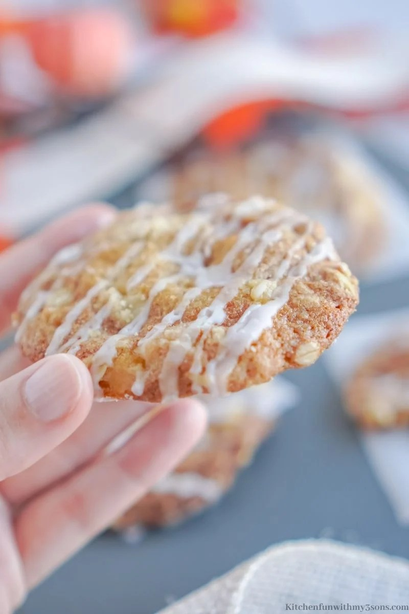A hand holding up one of the Caramel Apple Crisp Cookies.