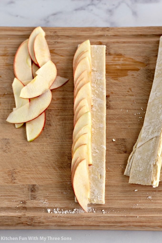 topping the strips of puff pastry with apples