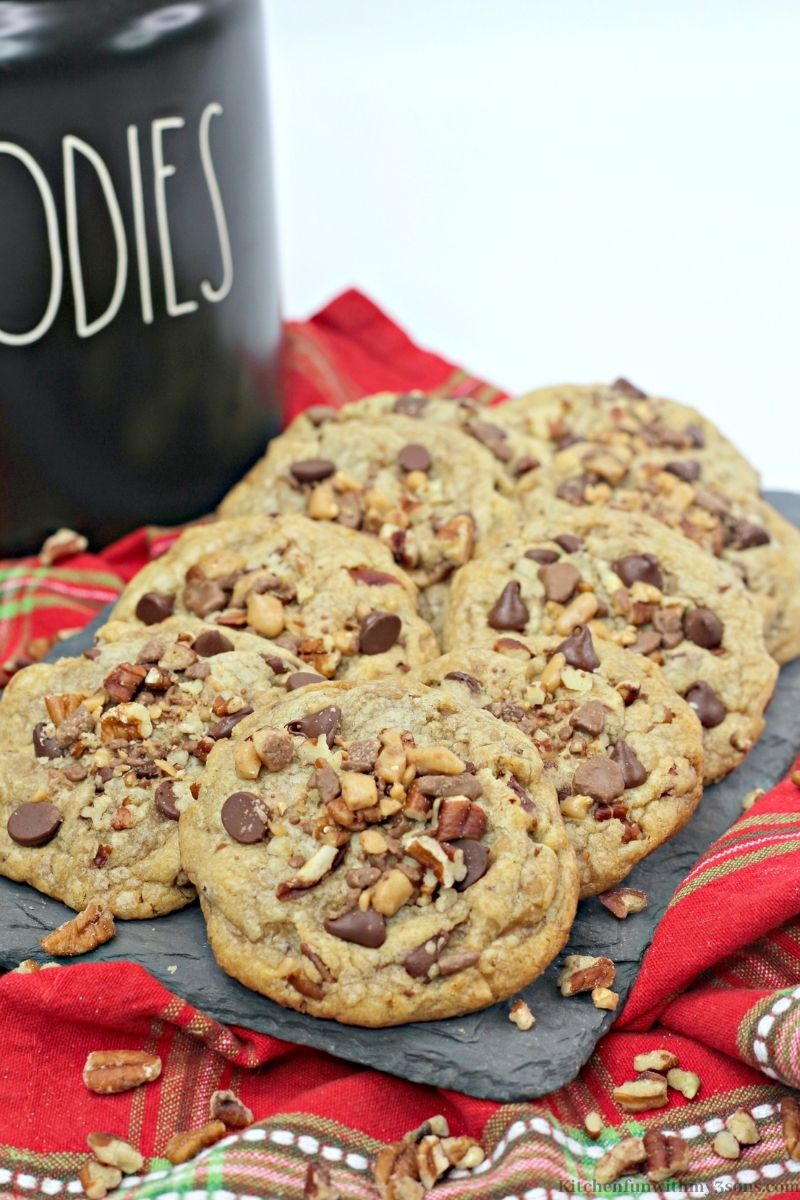 Chocolate Chip Pecan Toffee Cookies with a black cookie jar behind them.