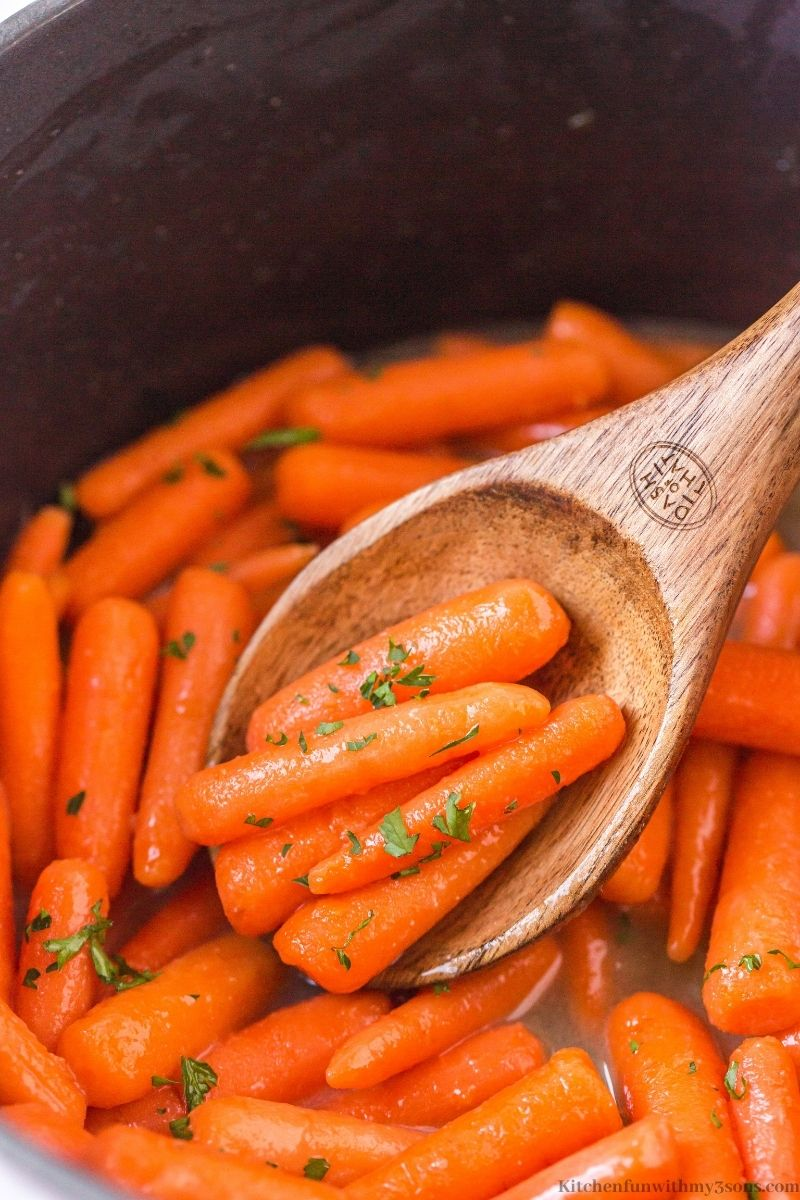 Wooden spoon lifting up some of the carrots.