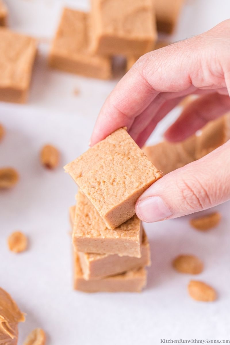 A hand holding a piece of the Easy Peanut Butter Fudge.