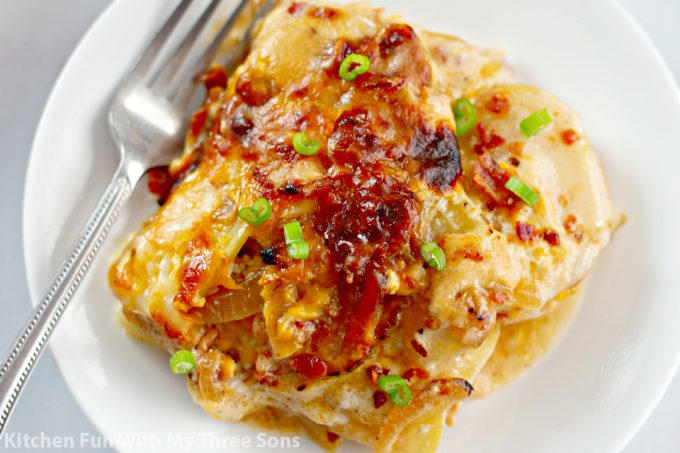 Cheesy Loaded Scalloped Potatoes on a white plate with a fork