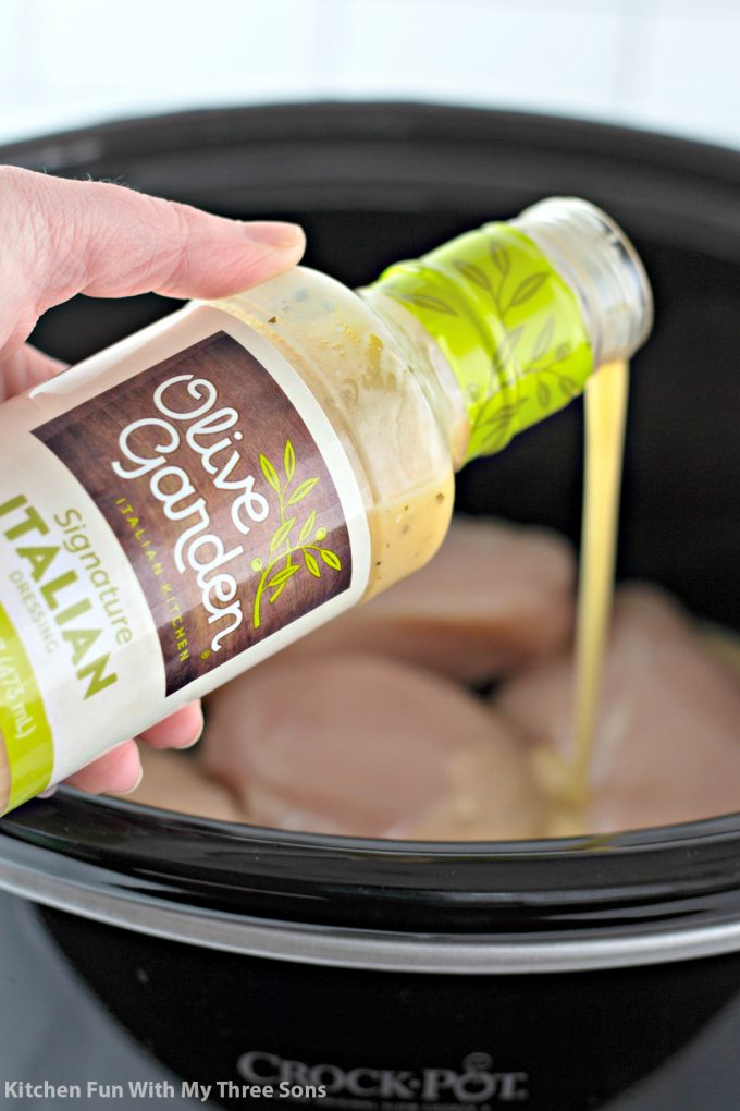 pouring Olive Garden dressing over chicken