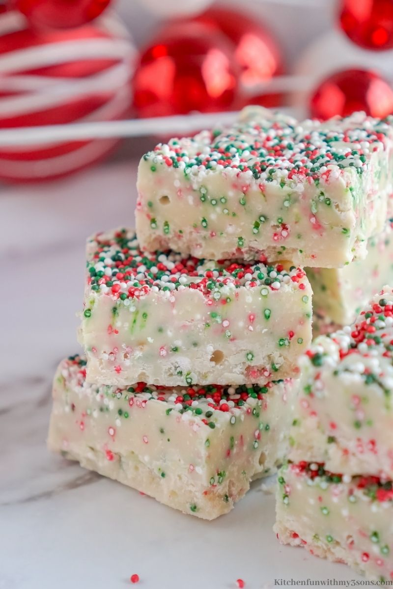 Christmas Cookie Fudge Recipe with red ornaments behind it.