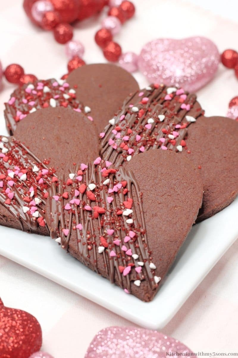 Chocolate Heart Shortbread Cookies with sparkling heart decorations around them.
