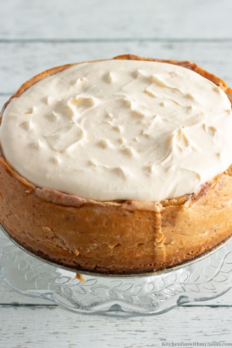 The cheesecake covered in a thick layer of whipped cream.