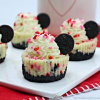 Mini Chocolate Cheesecakes with a mini oreo, frosting, and sprinkles
