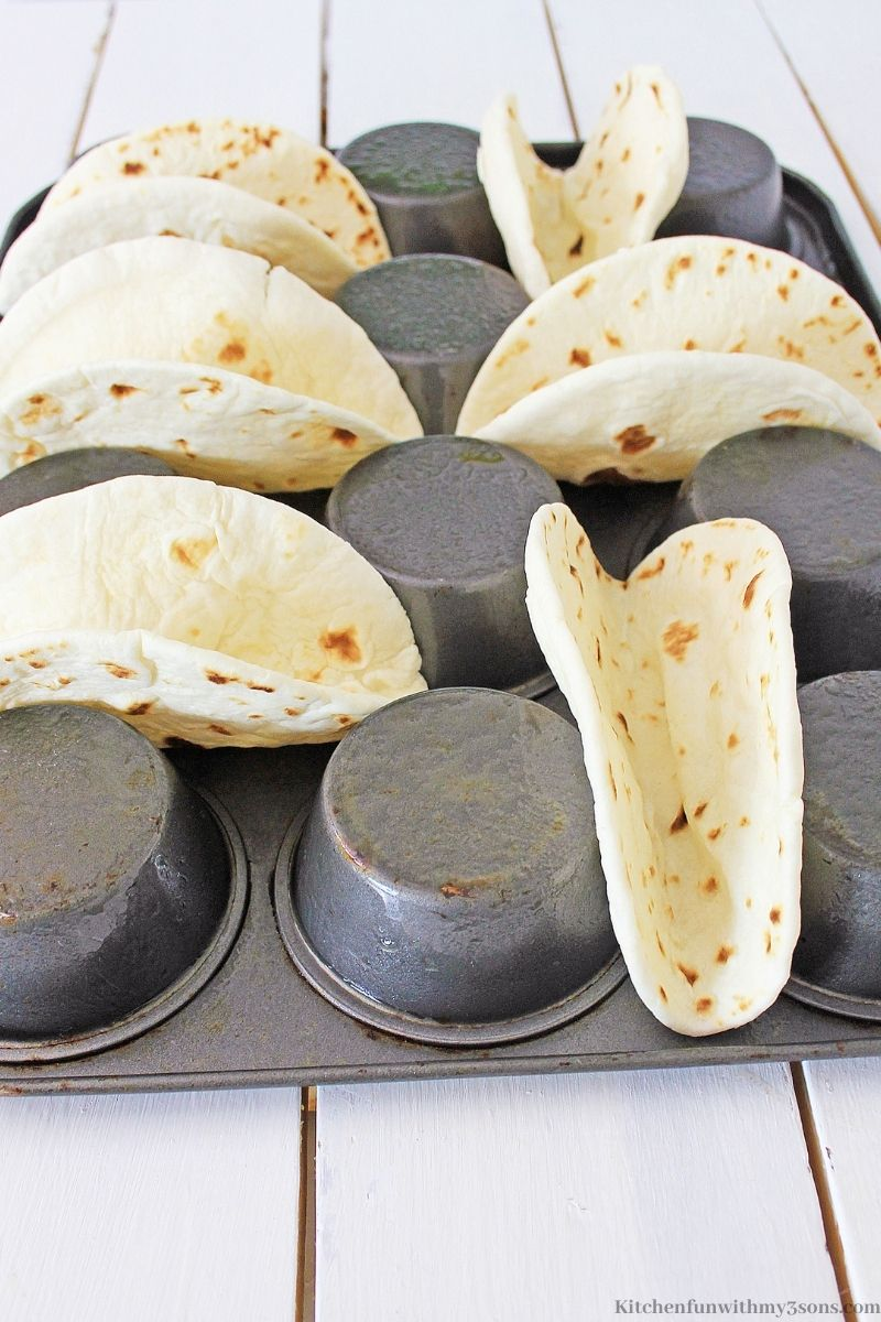 Flour Tortillas in between the muffin tin to form a shell.