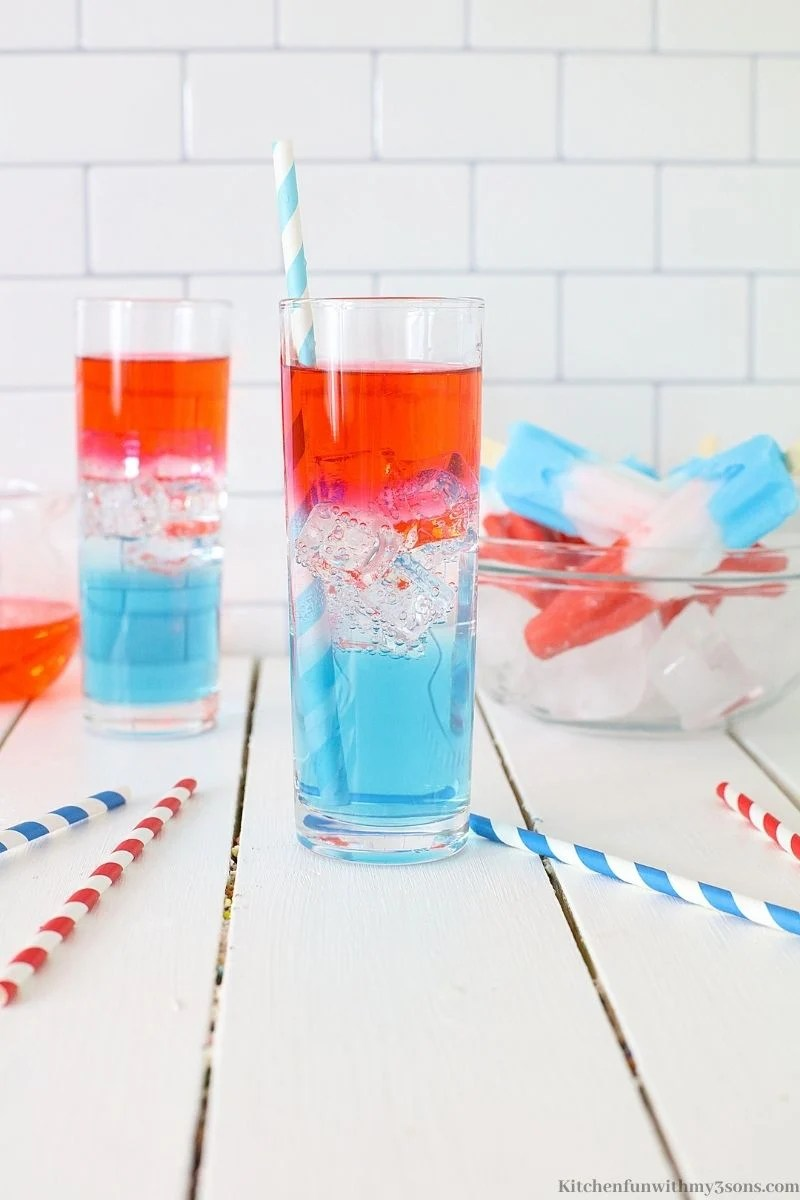 Two glasses of Rocket Pop Vodka Cocktail on a white wooden table with straws.