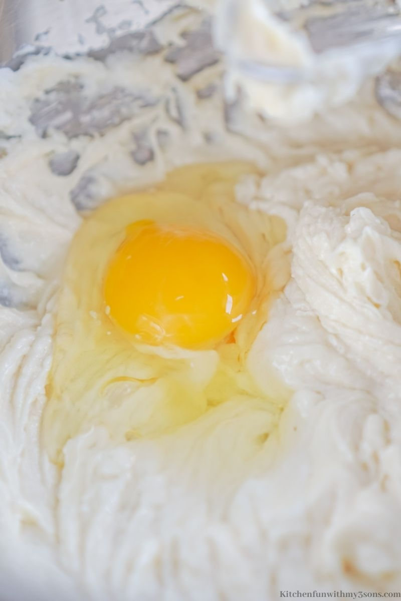 Adding the egg to the dough batter.
