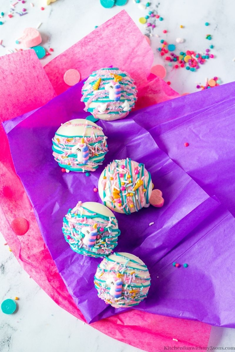The Unicorn Hot Chocolate Bombs on purple and pink tissue paper.