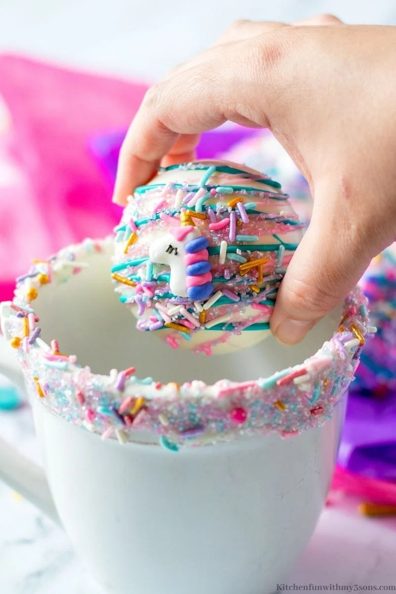 A hand getting ready to place a Unicorn Hot Chocolate Bombs in a mug.
