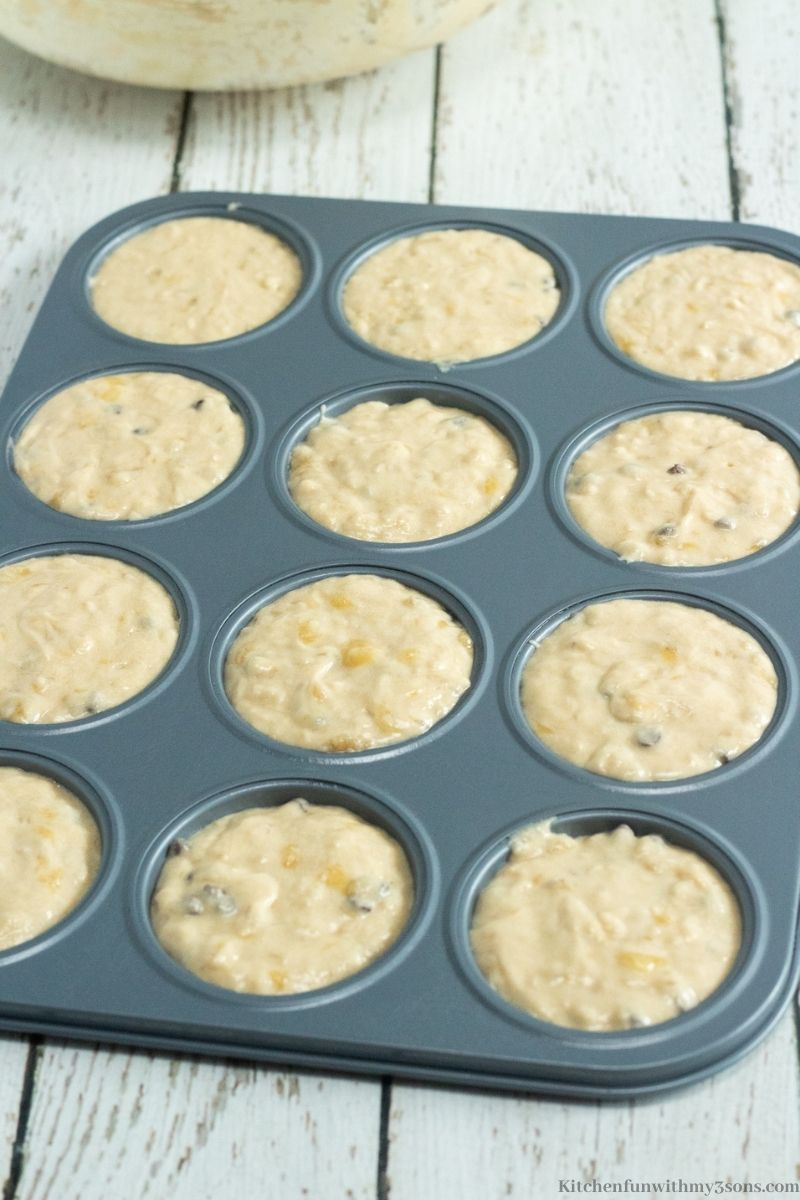 Pouring the batter into the prepared muffin pans.