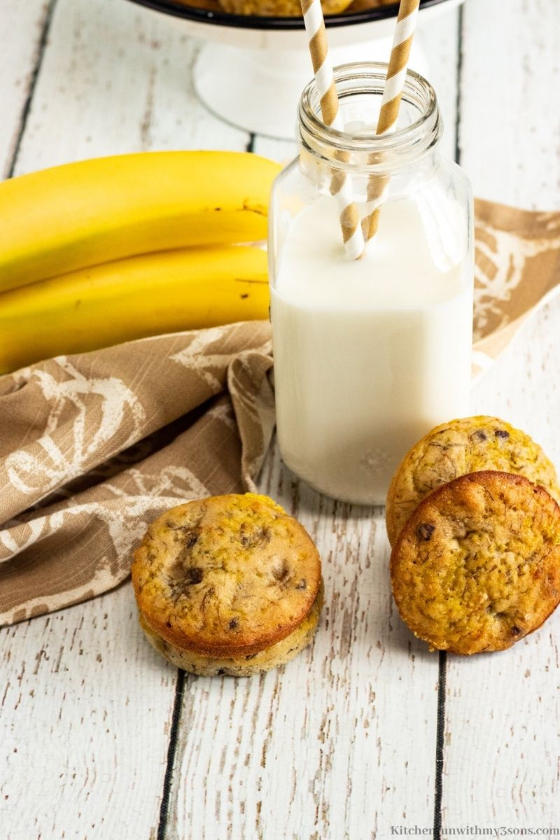 Chocolate Chip Banana Muffin Tops with bananas and a milk glass with straws inside.