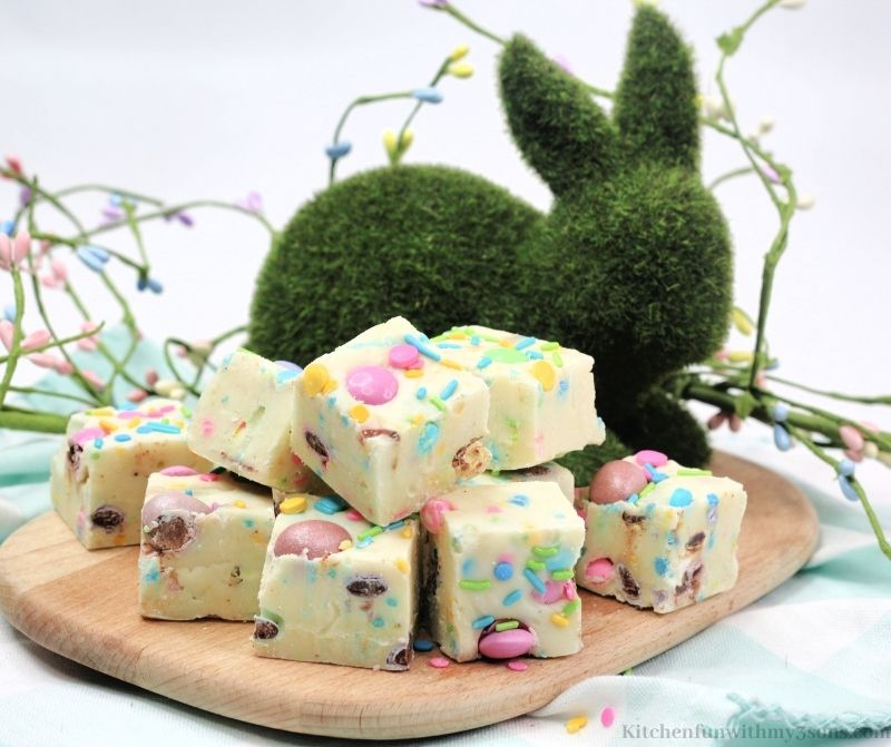 The fudge on a wooden cutting board with a bunny shaped bush decoration in the back.