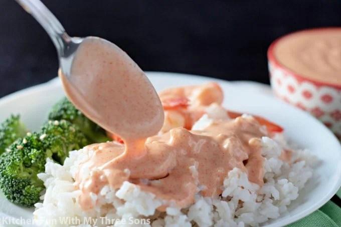 spooning Homemade Yum Yum Sauce over rice.