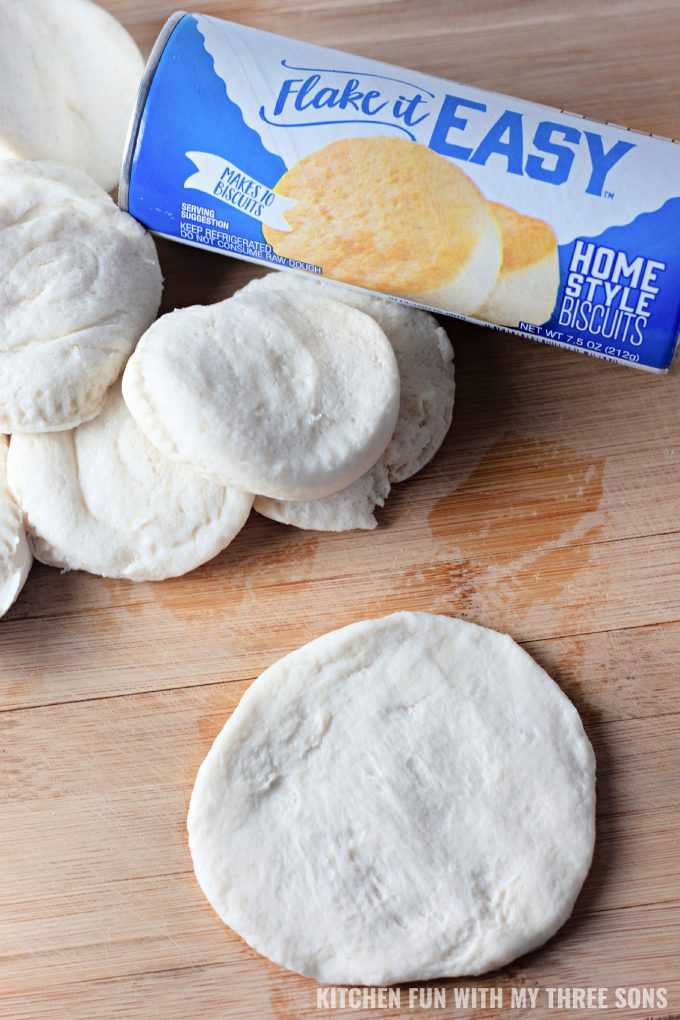 biscuit dough being pressed into flat circles.