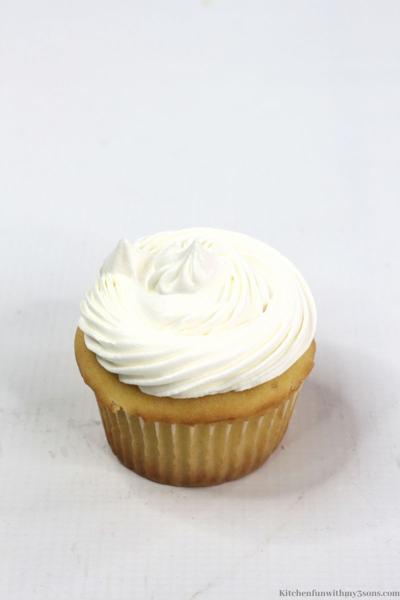 The cupcake topped with whipped cream.