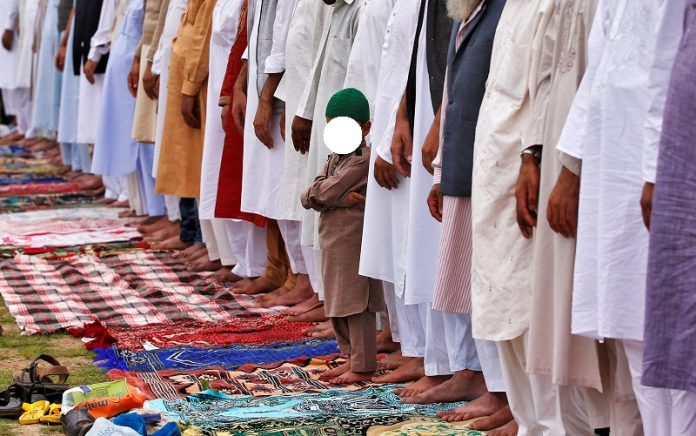 A Muslim boy looks on as he attends the Eid al-Fitr prayers in Srinagar